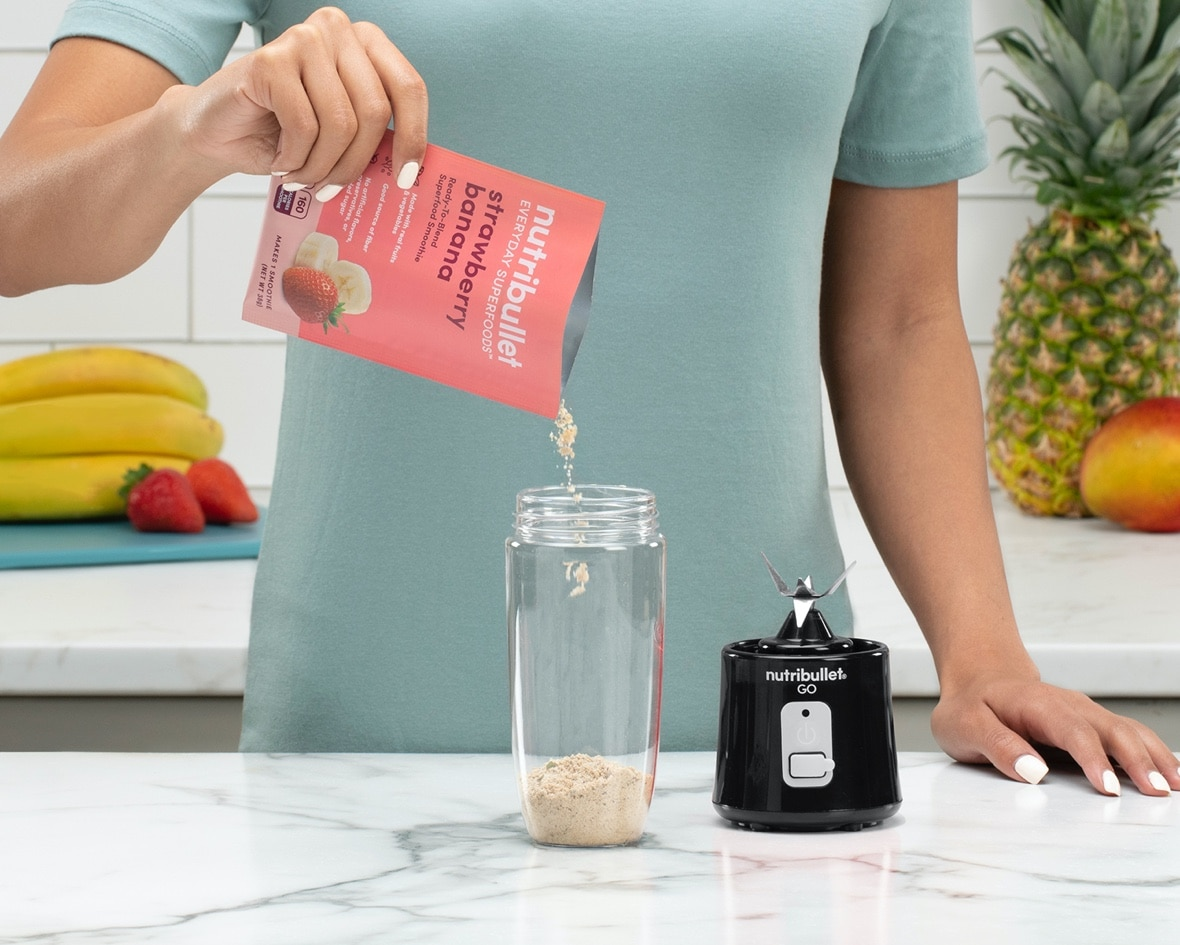Product preview 5 of 6. Thumbnail woman pouring strawberry banana pink packet into NutriBullet GO on counter with strawberries and bananas.